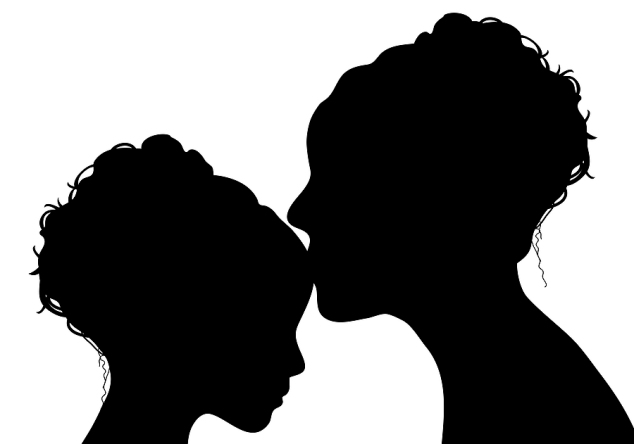 silhouette of mother kissing her daughter